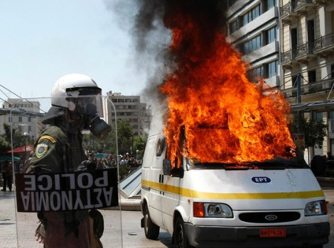 A policeman walks past a burning television broadcast van during riots at a May Day rally in Athens